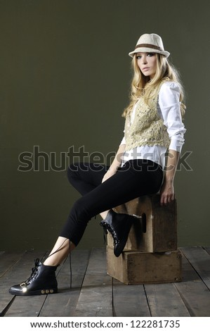 Full length beautiful fashion woman in hat sitting wooden cube  posing wooden floor