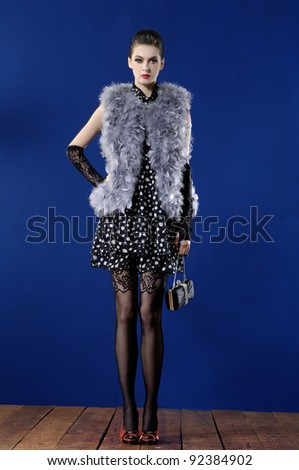 Full length beautiful fashion woman in jacket with fur posing wooden floor - stock photo