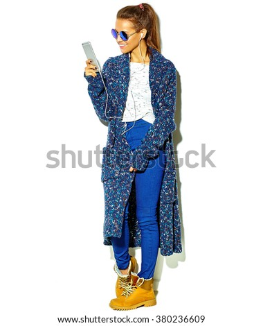 Full length beautiful happy cute smiling brunette woman girl in casual blue hipster summer clothes with no makeup isolated on white in sunglasses listening music in smartphone with headphones - stock photo