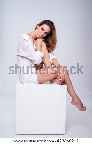 Full length beautiful leggy woman wearing boyfriend white shirt sitting on white box with blank empty copy space - stock photo