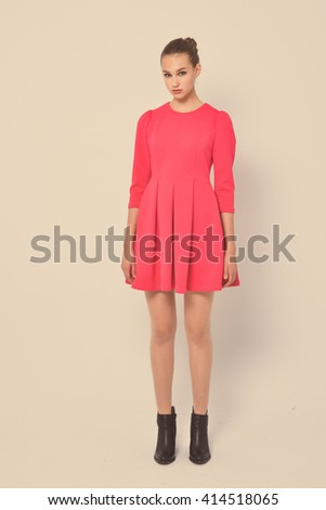 Full length beautiful young woman in red dress posing retro background  - stock photo