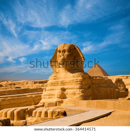 Full length body profile of Great Sphinx including head, feet with pyramid of Menkaure in background on a clear, blue sky day in Giza, Egypt empty with no people. Copy space