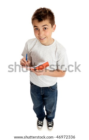 Full length boy jotting down notes in a small book or diary.  He is looking up from the book.  He is casually dressed in blue denim jeans and a plain grey t-shirt and smiling.  Shadows under feet. - stock photo