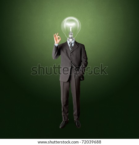 full length business male with lamp-head in suit shows OK - stock photo