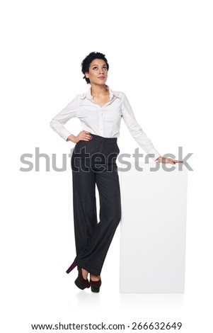 Full length business woman standing leaning at blank white board, looking up, isolated on white background - stock photo