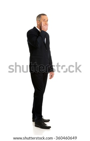 Full length businessman covering mouth