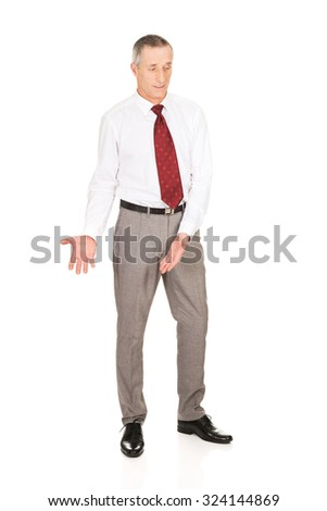 Full length businessman showing copyspace on the floor - stock photo