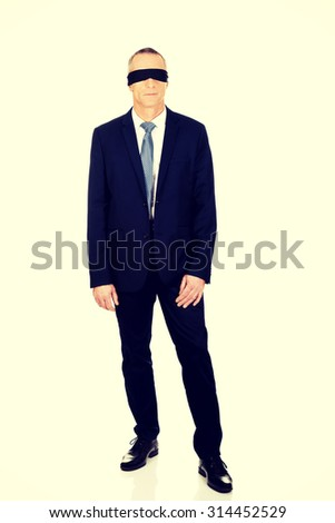 Full length businessman with band on eyes. - stock photo