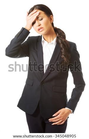 Full length businesswoman having huge headache. - stock photo