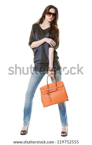 Full length casual fashion women wearing sunglasses with bag on black background - stock photo