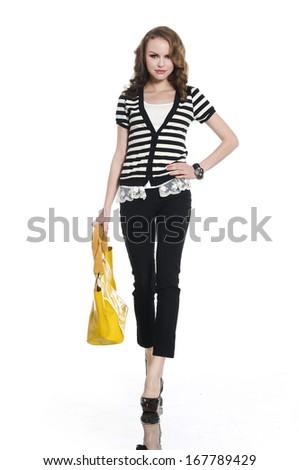 Full length casual young fashion holding yellow bag walking - stock photo