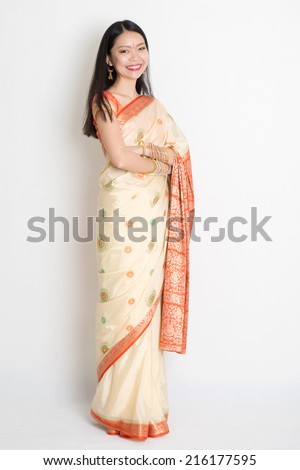 Full length confident fair skin tone Asian Indian female smiling and standing on plain background. - stock photo