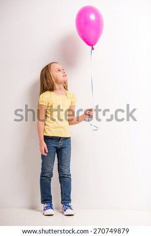 Full length. Cute little girl holding pink balloon on grey background. - stock photo
