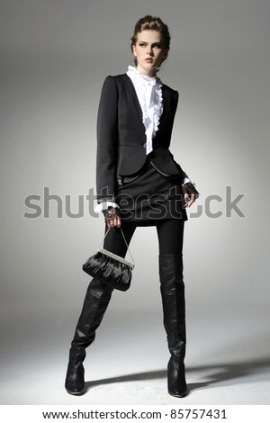 full-length fashion girl with handbag posing on light background - stock photo