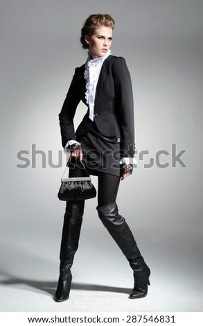 full-length,fashion model clothes holding handbag posing-gray background  - stock photo