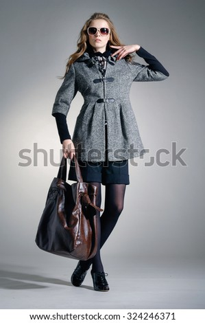 full-length fashion model in autumn/winter clothes holding handbag posing  - stock photo
