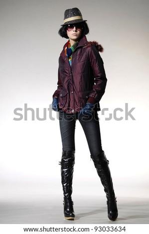 full-length fashion model in fashion dress posing on gray background - stock photo