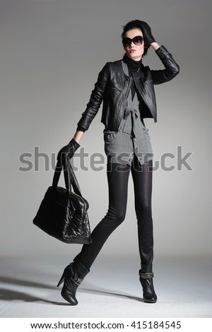 full-length fashion model in modern clothes holding handbag posing   - stock photo