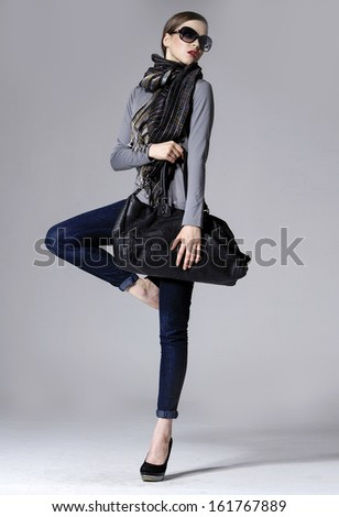 full length fashion model in sunglasses with bag standing . Isolated on gray  - stock photo