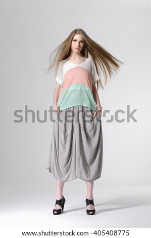 Full length fashion model wearing modern dress posing in light background - stock photo