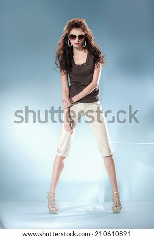 Full length fashion model wearing modern sunglasses posing in light background - stock photo