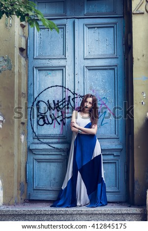 Full length fashion portrait modern woman standing near old door