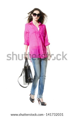 full-length fashion woman in jeans with bag walking in studio  - stock photo