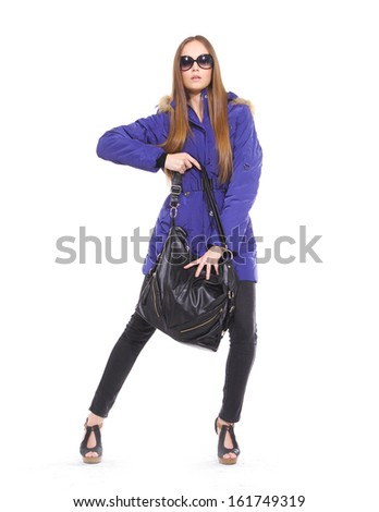 Full length fashionable woman in blue coat with sunglasses posing