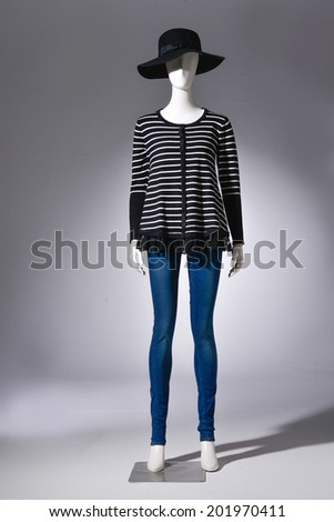 full-length female clothing in jeans with black hat on mannequin on gray background - stock photo
