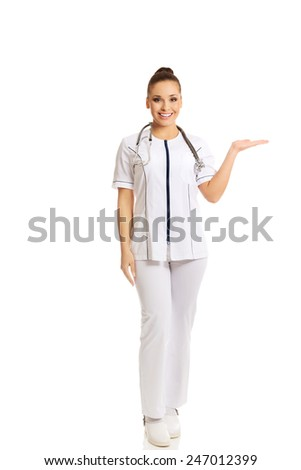 Full length female doctor presenting copyspace on the right. - stock photo