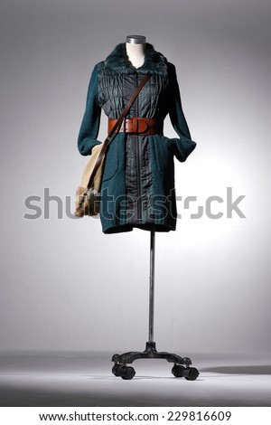 Full length female jacket in mannequin with bag isolated on light background - stock photo