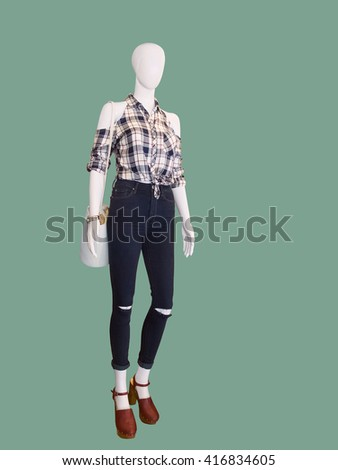 Full length female mannequin dressed in jeans and a checkered shirt. Isolated on white background. No brand names or copyright objects. - stock photo