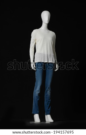 full-length female mannequin dressed in white dress and jeans on black background  - stock photo