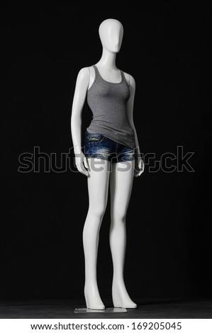 full-length female mannequin in shirt dress and shorts on black background
