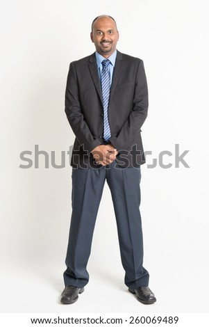 Full length friendly Indian businessman in formal suit looking at camera, standing on plain background. - stock photo