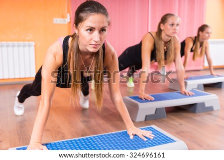 Full Length Front View of Group of Young Women Doing Push Ups or Plank Exercises in Step Class Using Step Platforms and Looking Straight Ahead with Serious Expressions - stock photo