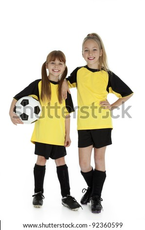 Full length front view of two young girls in soccer uniforms, holding soccer ball on white. - stock photo