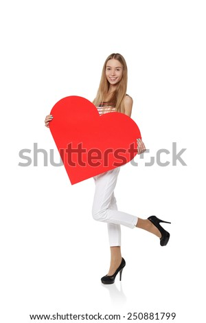 Full length girl holding up a red cardboard heart, isolated on white background - stock photo