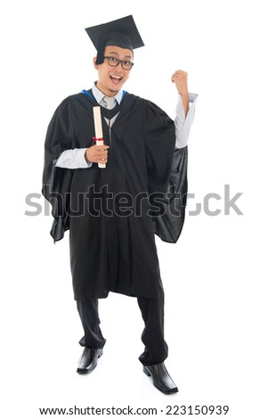 Full length happy southeast Asian university student in graduation gown, standing isolated on white background.