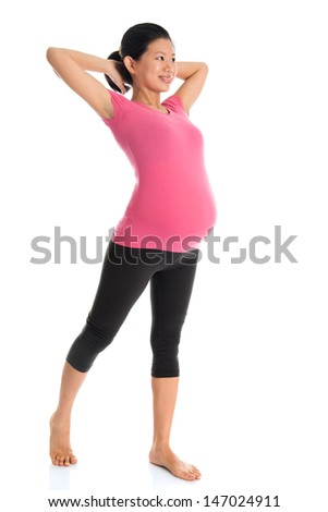 Full length healthy Asian pregnant woman doing yoga exercise stretching at home, full body isolated on white background.