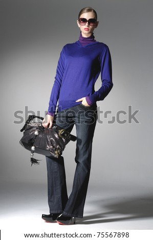 Full length High fashion model with bag posing in the studio