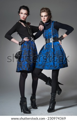 full-length high young stylish two model in fashion dress posing in the studio  - stock photo