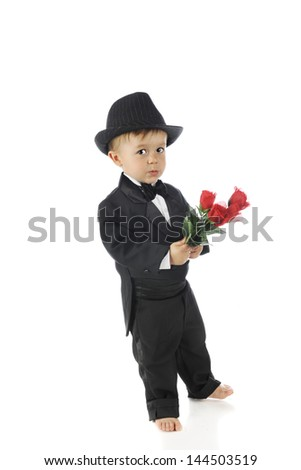 Full-length image of a barefoot toddler looking skittish in his black tux as he carries a bouquet of red roses.  On a white background.