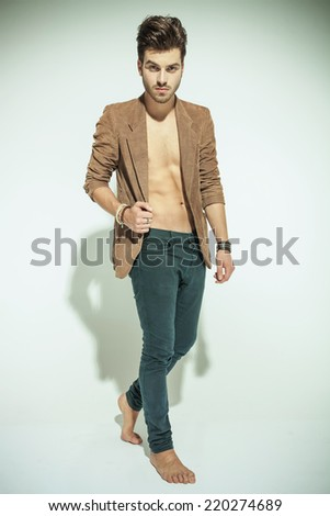 Full length image of a fashion man walking on grey background, pulling his jacket while looking at the camera - stock photo