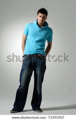 Full length image of a handsome young guy standing on gray background - stock photo
