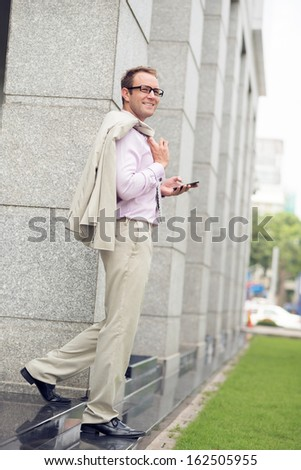 Full-length image of a young businessman with a smartphone in hands standing outside - stock photo