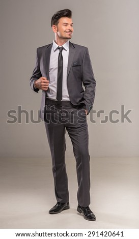 Full length image of a young man in dark suit on gray background. Studio shot. - stock photo