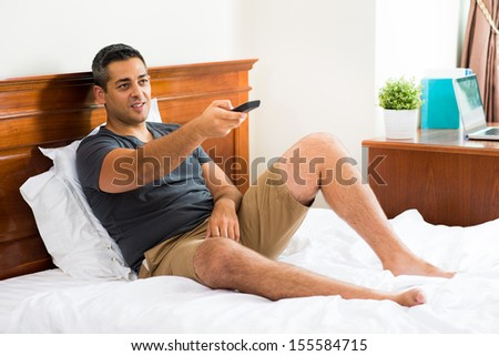 Full-length image of a young man watching TV at home - stock photo