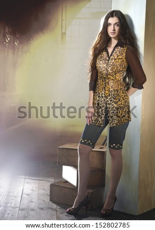 Full length image of an attractive young girl posing on wooden floor