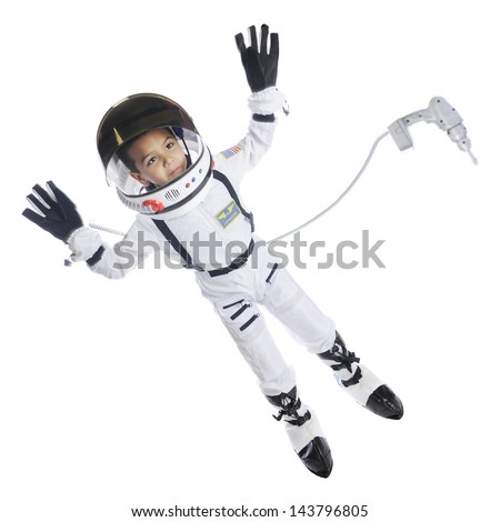 Full length image of an elementary astronaut in full gear floating in space.  He has an attached dress floating nearby.  On a white background. - stock photo